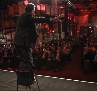 Motivationstrainer / Mental Coach / Motivationscoach Dirk Schmidt auf der Bühne, stehend auf einem Stuhl