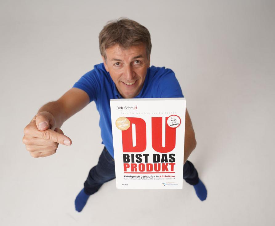 """Motivationstrainer Dirk Schmidt mit einem Plakat in der Hand, Schirftzug """"DU bist das Produkt"""""""